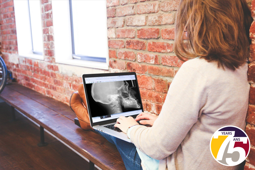 Photo of a woman working on laptop with a skull on the screen