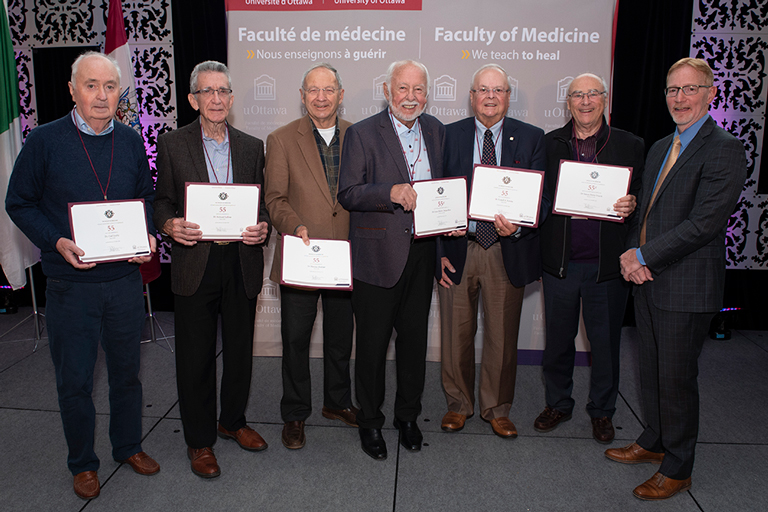 The MD class of 1964 holding their milestone certificates.