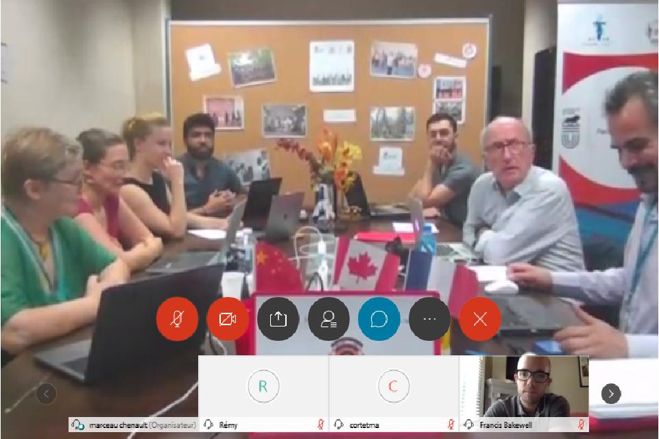 Un groupe de professeurs et d'étudiants sont assis autour d'une table durant une videoconference