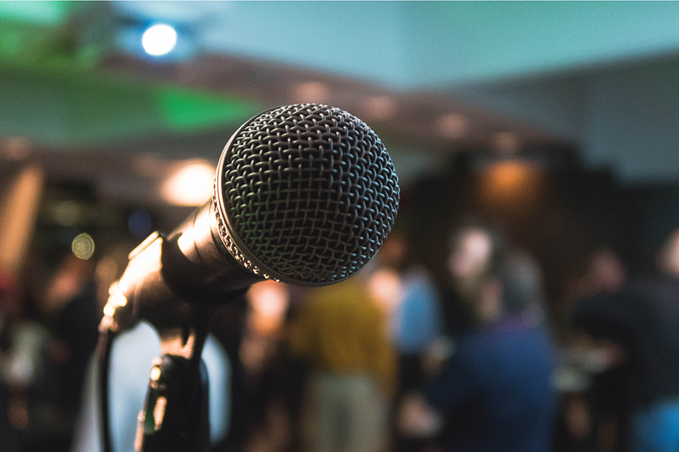 A microphone on stage in front of a crowd.