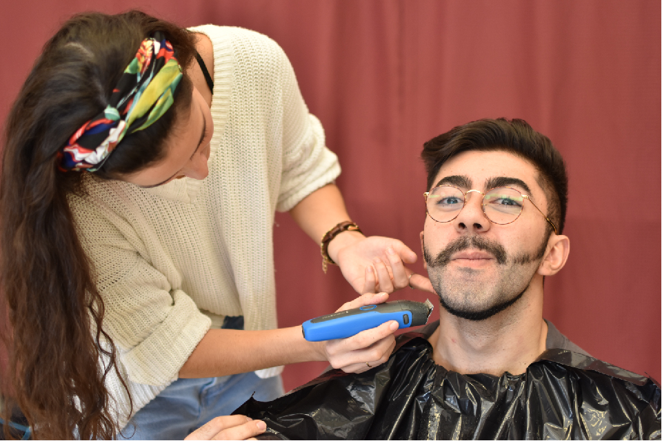 Lara Pereira shaves Ricardo Viltakis' beard with an electric razor.