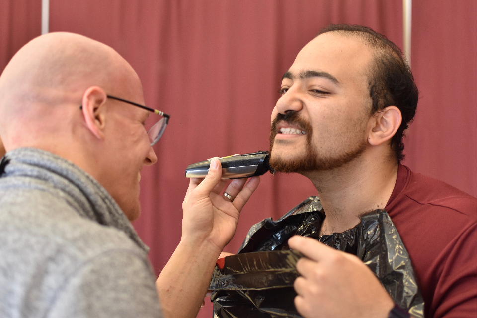 Dave DeLaunay shaves the chin of Mina Boshra with an electric razor.