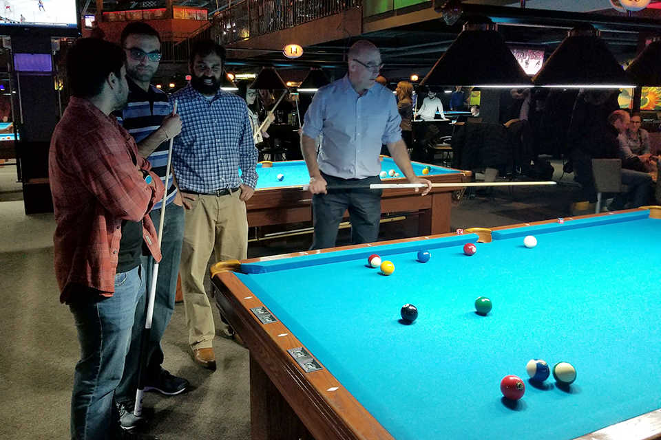 Four people playing pool