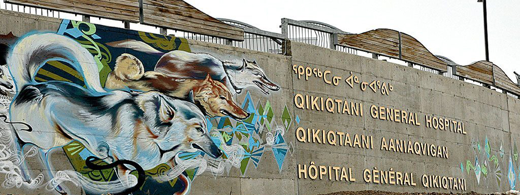A wall outside the Qikiqtani General Hospital depicting a mural and the name of the hospital