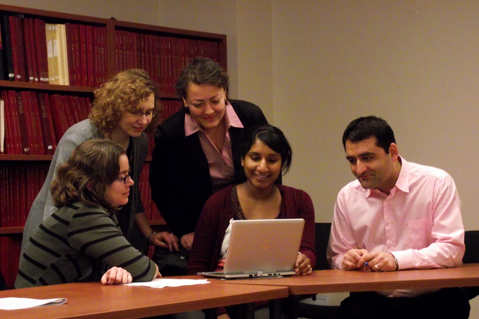 Five residents looking at the screen of a laptop computer in a conference room.