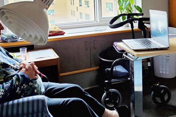 Un résident d'une maison de soins de longue durée regarde un spectacle sur un ordinateur portable