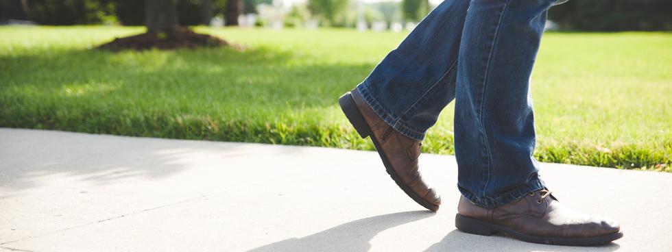 Les jambes d'un homme en jeans marchant en plein air.