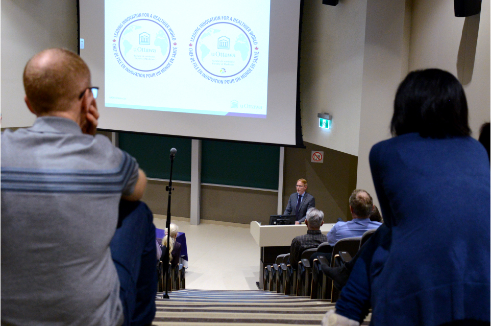 Two people sit, facing away from the camera, in the back row of a large auditorium. Between them, the figure of Dr. Bernard Jasmin can be seen at a podium at the front of the auditorium. A large screen at the front of the auditorium shows a projection of