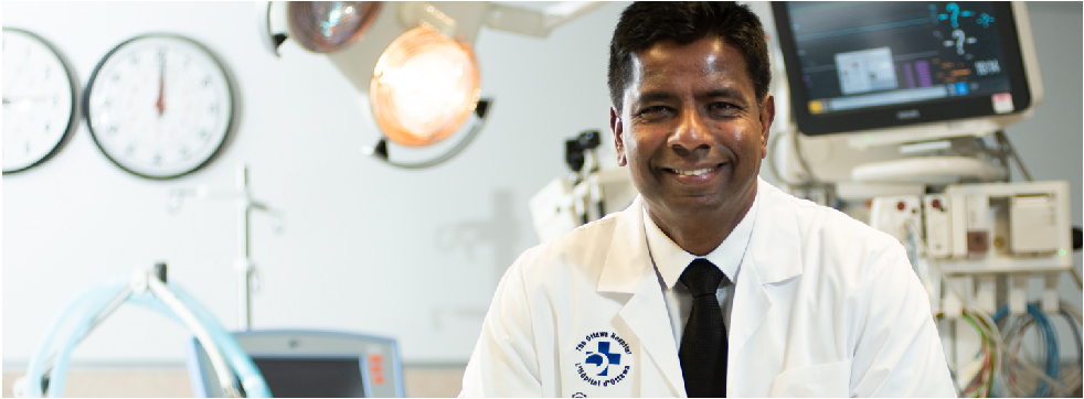 Dr. Venk, wearing a lab coat, stands in front of a vital signs monitor, with bright lights in the background