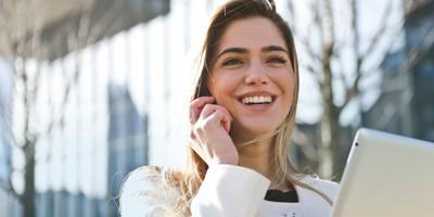 Jeune femme souriante parle au cellulaire et tiens une tablette de l'autre main