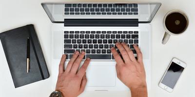 Mains d'un homme qui écrit à l'ordinateur placer sur une table avec un cellulaire, un carnet et un café