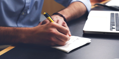 Un homme assis devant un ordinateur prend des notes sur un papier