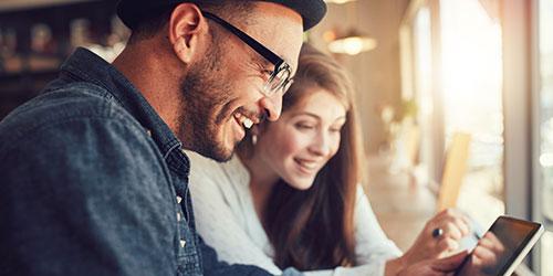 Un homme et une femme dans un café, utilisent une tablette numérique