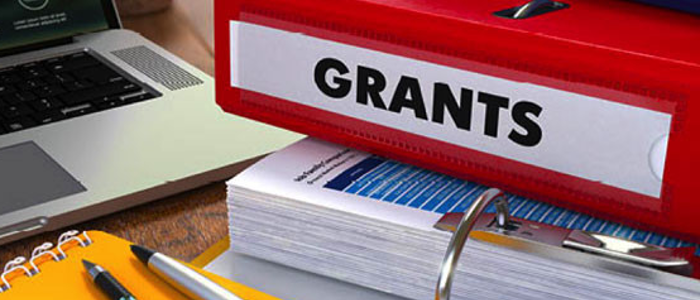 "Stacked binders, including a red one labelled ""Grants"""