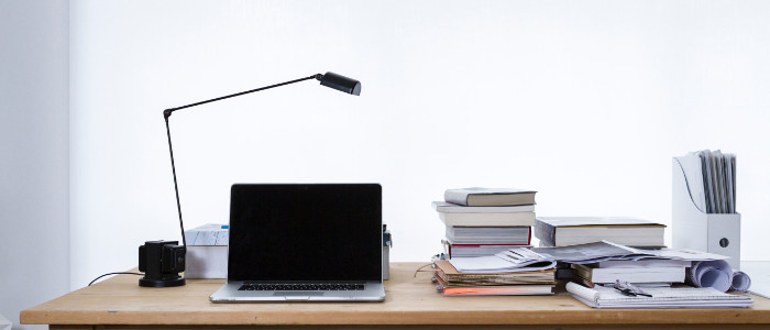 A desk with a laptop, skinny lamp, numerous books and papers in a stark white room.