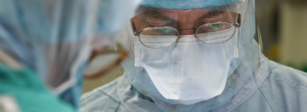 A surgeon looking down with a look of concentration.