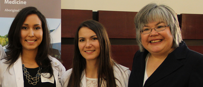 Two medical students stand together at the White Coat Ceremony with Dr. Darlene Kitty