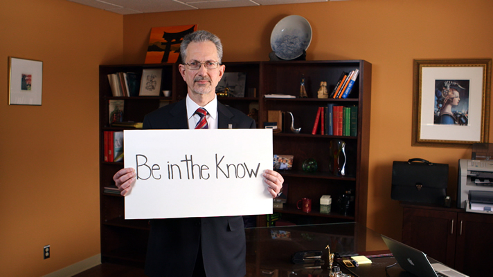 Dr. Jacques Bradwejn, Dean of medicine, holding a sign: Be in the know