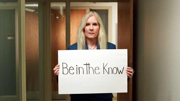 Dr. Melissa Forgie, Vice-dean, holding a sign: Be in the know