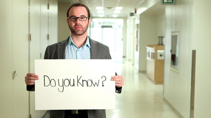Male student holding a sign: Do you know?