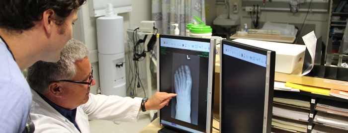 Preceptor explaining something to a student, about an x-ray photo of a foot on a computer monitor