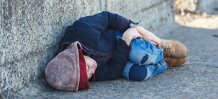 Jeune garçon sans-abri dormant sur le pont