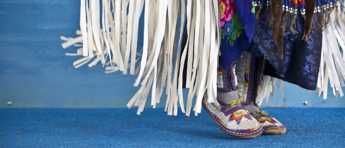 A close-up of a traditional dancer, regalia and mocassins