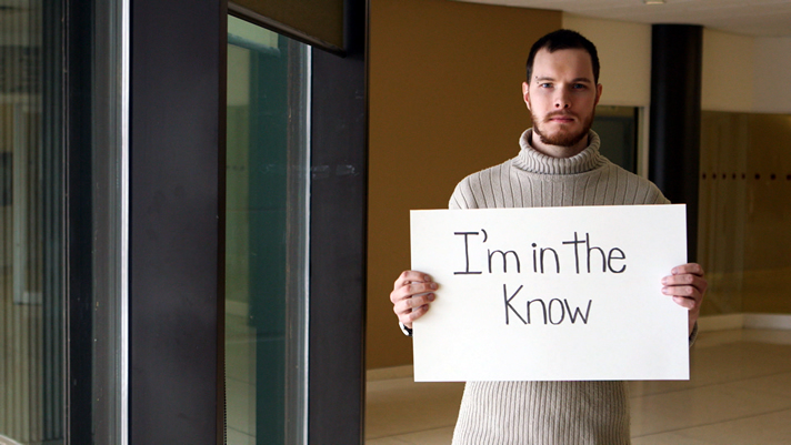 Male student holding a sign: I'm in the know?