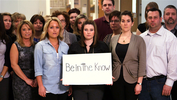 """Support staff holding a sign: Be in the know"""""""